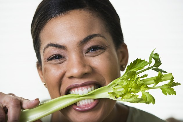 Woman biting celery stalk