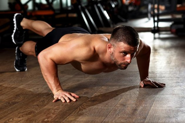 Muscular man doing a pushups at gym.