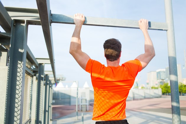Male runner in bright t-shirt training hard in urban setting