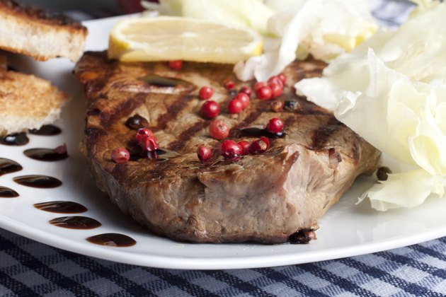 slice of grilled rump steak with green and pink pepper