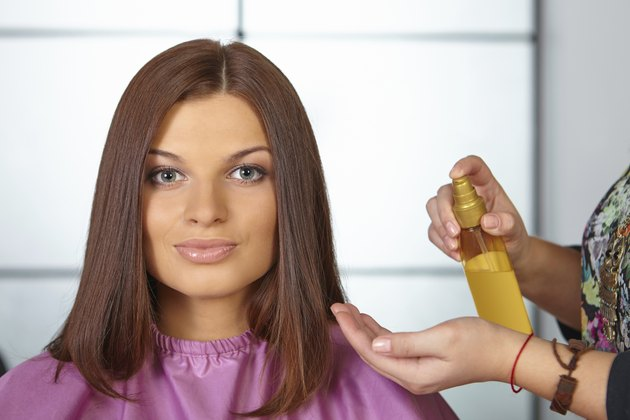 Hair salon. Women`s haircut. Use of cosmetic oil.