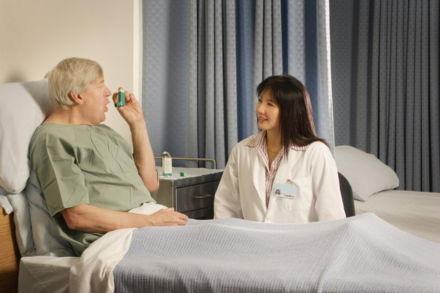 A health care professional supervises patient using inhaler
