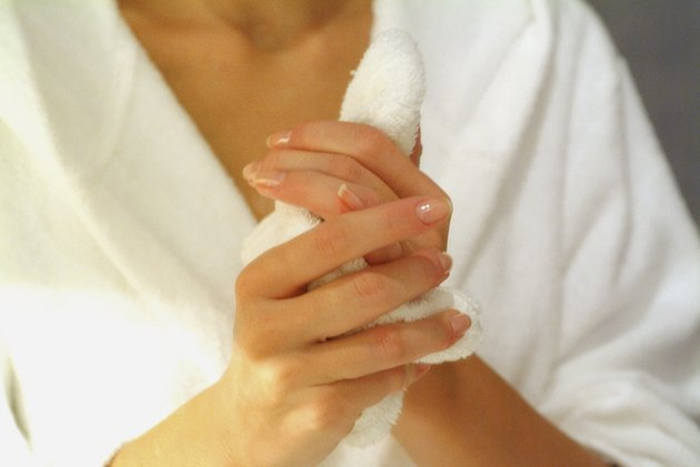Mid section view of a woman rubbing his hands with a towel