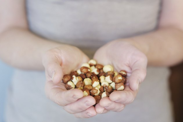 Middle age woman holding hazelnuts in her hands
