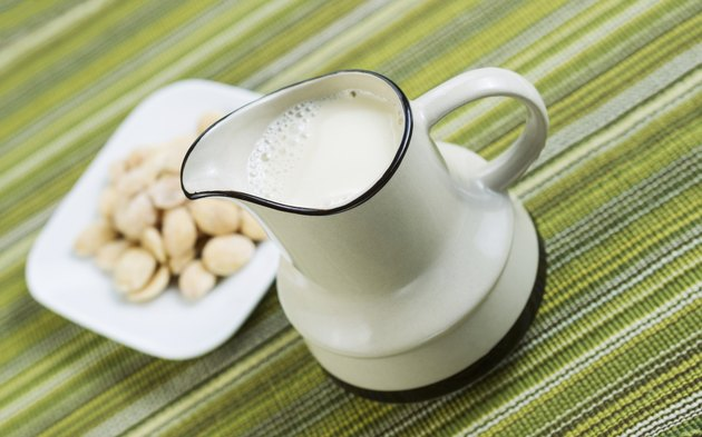 Almond milk in pourer with Almonds