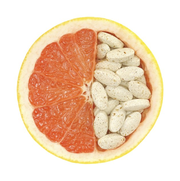 Close up of grapefruit and pills isolated