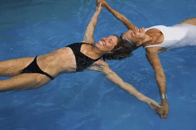 Mother and adult daughter floating in swimming pool