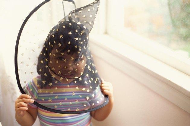 Girl wearing funny hat near window