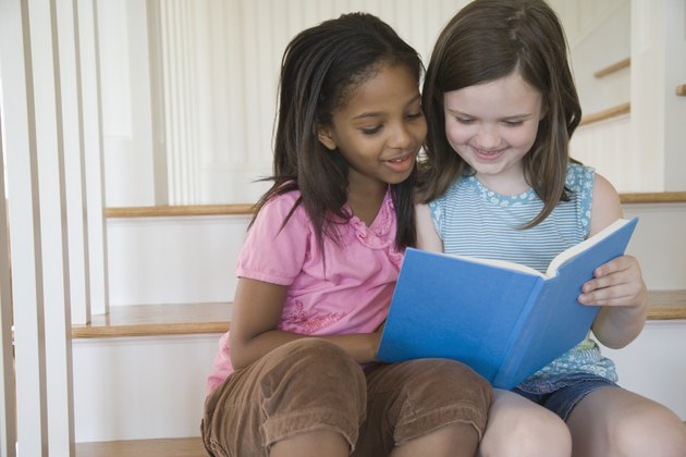 Close-up of two girls reading a book
