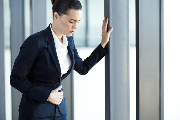 young businesswoman having stomach ache