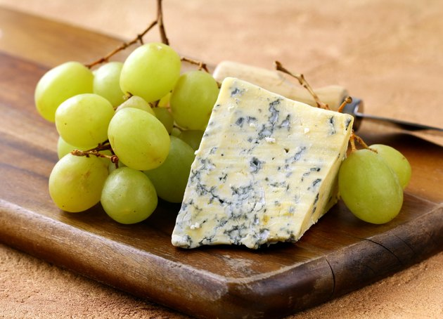 blue cheese and white grapes on a wooden board