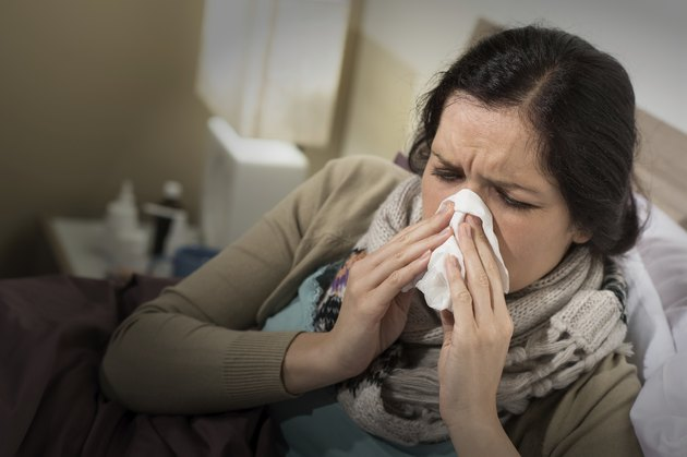 Woman having bad cold blowing her nose
