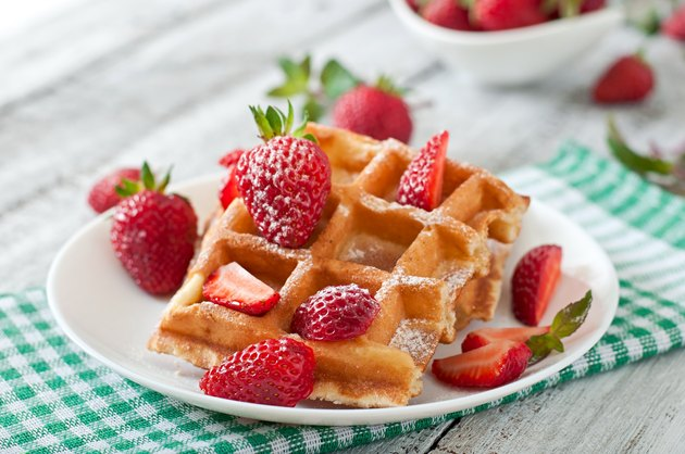 Belgium waffles with strawberries and mint on white plate