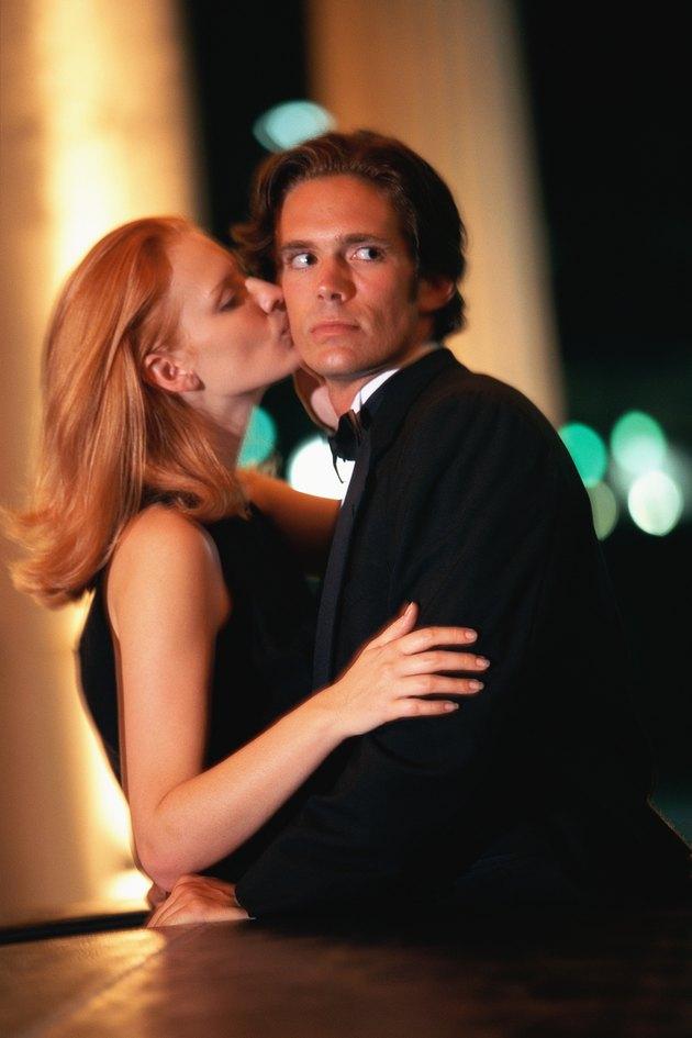 Woman kissing man on cheek, man turning head