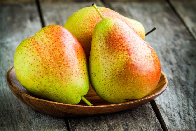 Three fresh ripe organic pears in a wooden bowl