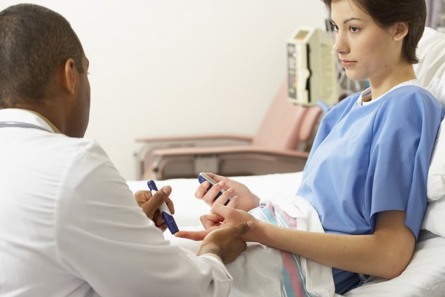 Rear view of a male doctor taking a blood sample from a female patient's finger