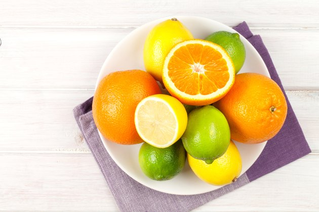 Citrus fruits on plate. Oranges, limes and lemons