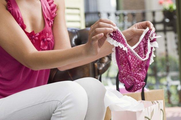 Woman holding panties over shopping bag