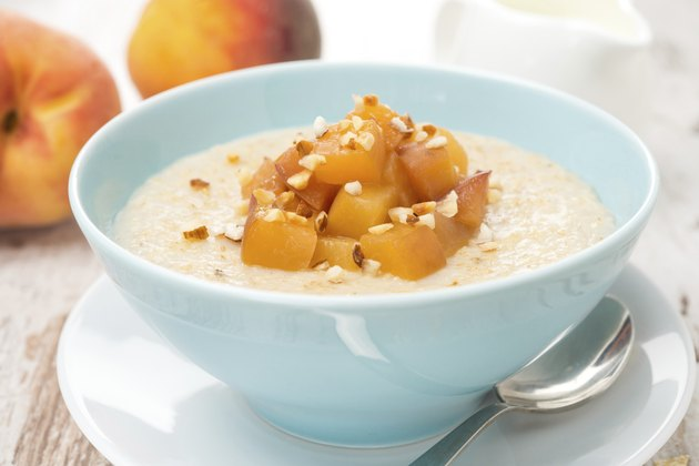 oatmeal with caramelized peaches in a bowl, jug of yogurt