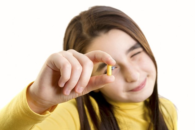 young girl holding capsule