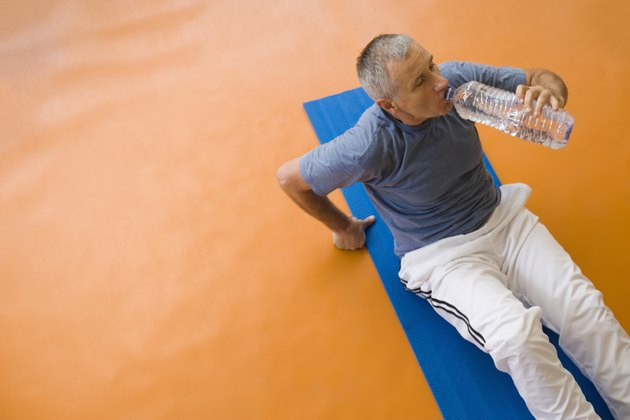 Man sitting on exercise mat, drinking water