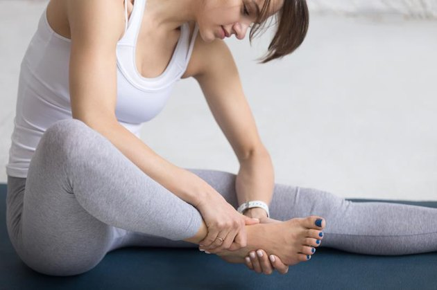 Beautiful young woman massaging her foot during sport work out indoors, close-up