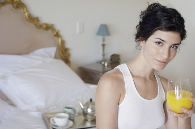 Young woman drinking orange juice on bed (portrait)