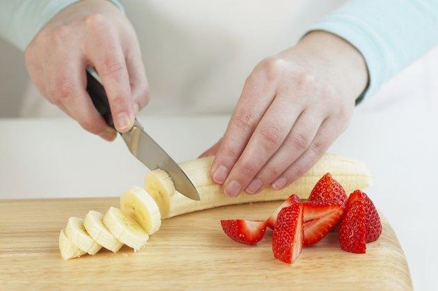 Using a knife to slice a banana, close up