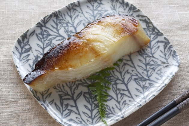 Cooked fish on a plate with chopsticks, overhead view