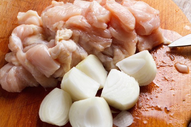 Chicken cubes and onion on the kitchen cutting board