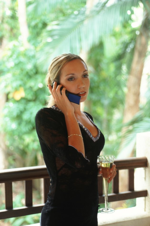 Businesswoman using mobile phone, holding wine glass