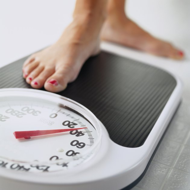 Woman stepping on bathroom scale, low section, close-up of foot