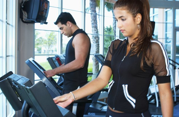 Man and woman exercising on exercise machine in a gymnasium