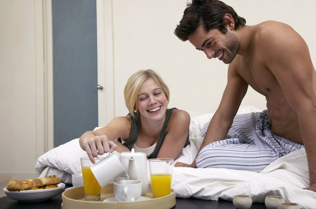 Young couple on bed having breakfast, woman pouring milk