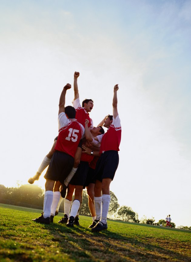 Soccer team raising their arms in triumph