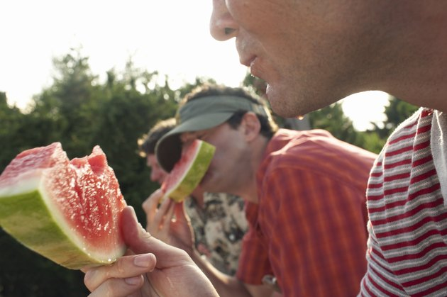 Man eating watermelon outdoors with male friends, close-up