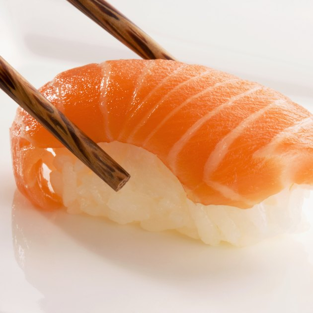 Close-up of Nigiri sushi with salmon held between chopsticks