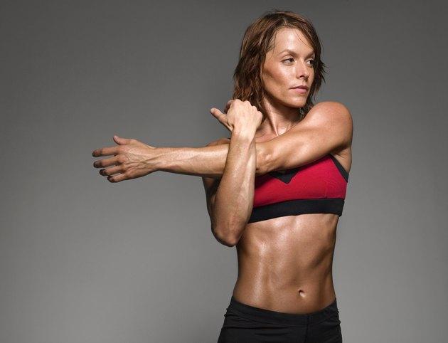 Female athlete stretching, studio shot