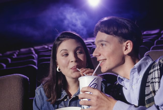 Teenage couple (16-17) sitting in cinema with popcorn, sharing soda