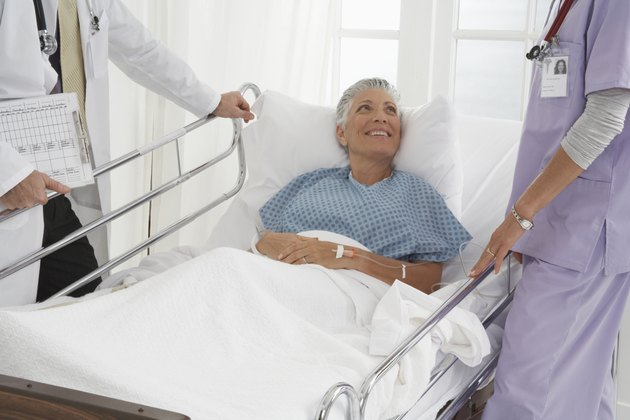 Patient in hospital bed speaking to Doctor and Nurse, smiling