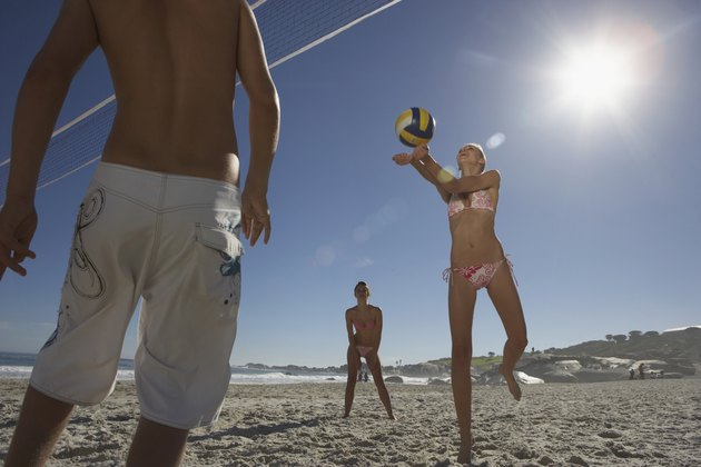 Teenage boy (15-17) and two young women playing volleyball on beach