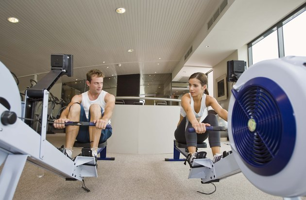 Man and woman on rowing machines at gym