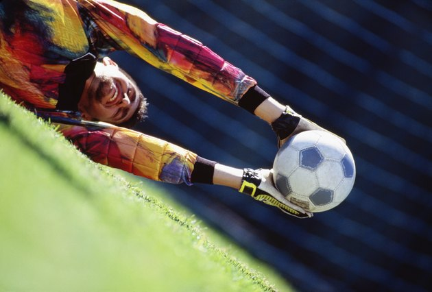 Soccer goalie lunging and catching ball