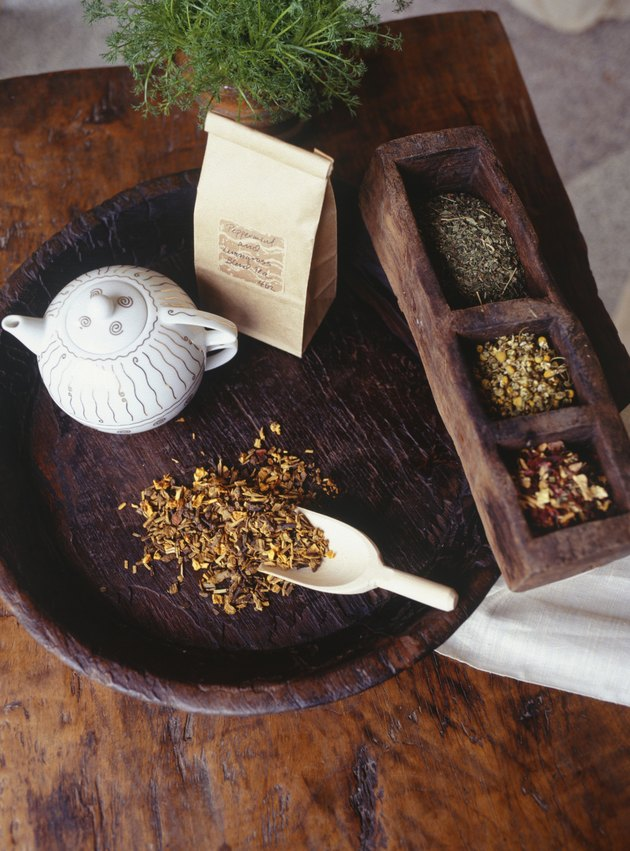 Teapot and peppermint tea lying on wooden tray, elevated view