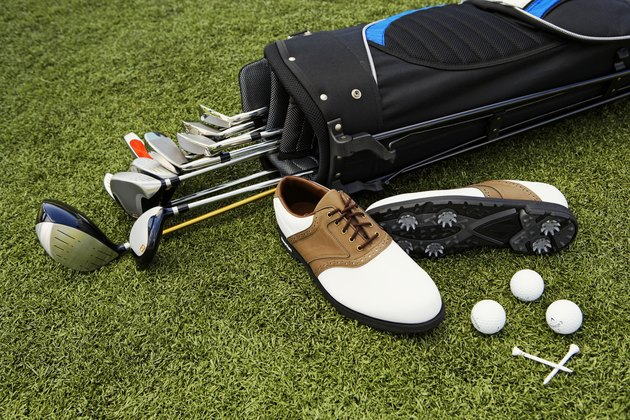Golf clubs, golf bag, shoes, balls and tees on artificial turf