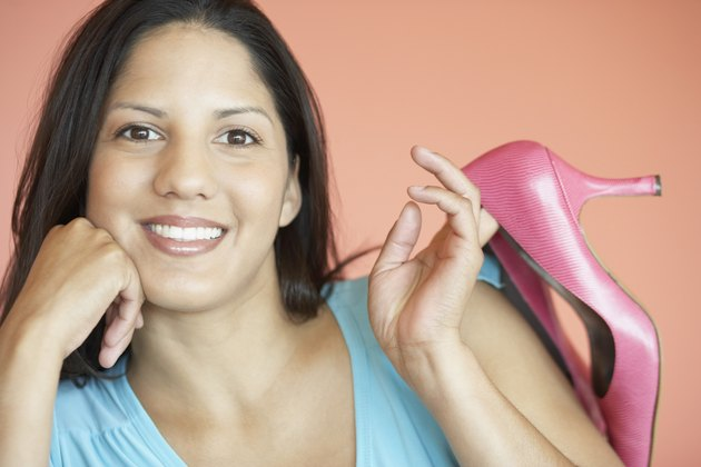 Portrait of a young woman holding a pair of shoes over her shoulder