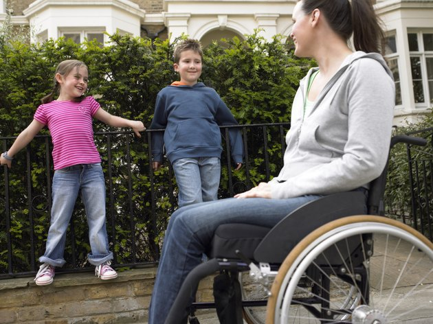 Mother in wheelchair in street with daughter and son (7-9) smiling