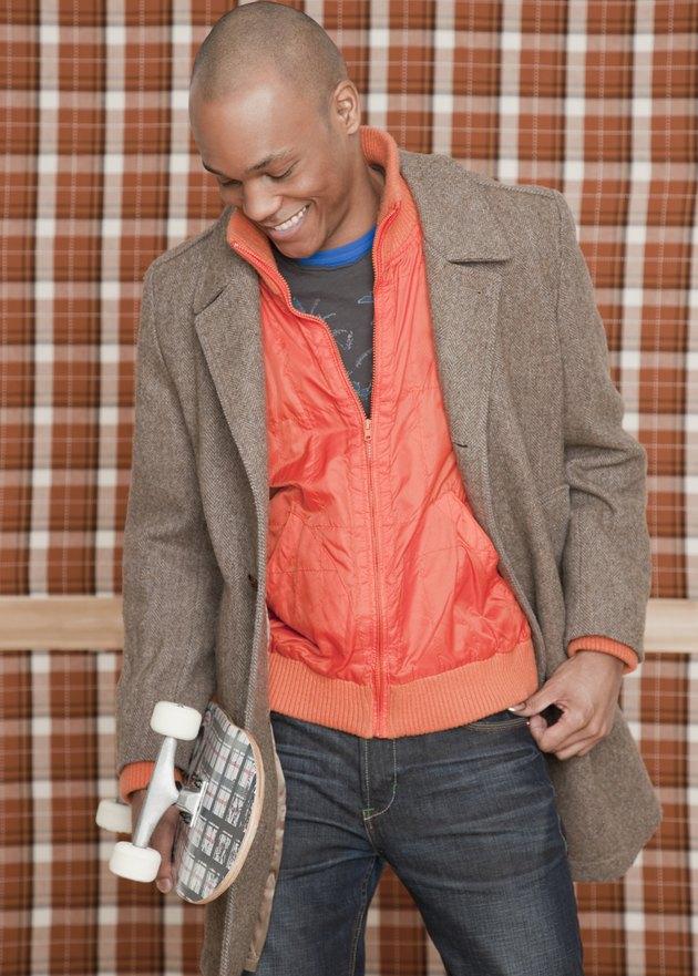 African man holding skateboard