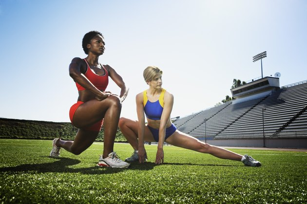 Athletic women stretching on field