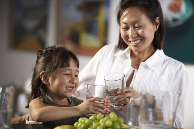 Close-up of a mid adult woman and her daughter toasting with glasses